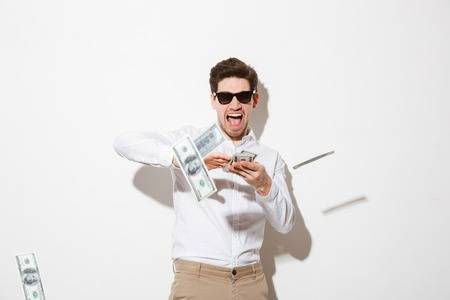 99258468-portrait-of-a-happy-young-man-in-sunglasses-throwing-money-banknotes-at-camera-isolated-over-white-b